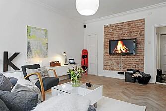 KONTRAST: Den tøffe murveggen harmonerer med kjøkkenøya og er en stilig kontrast til de lyse veggene.
