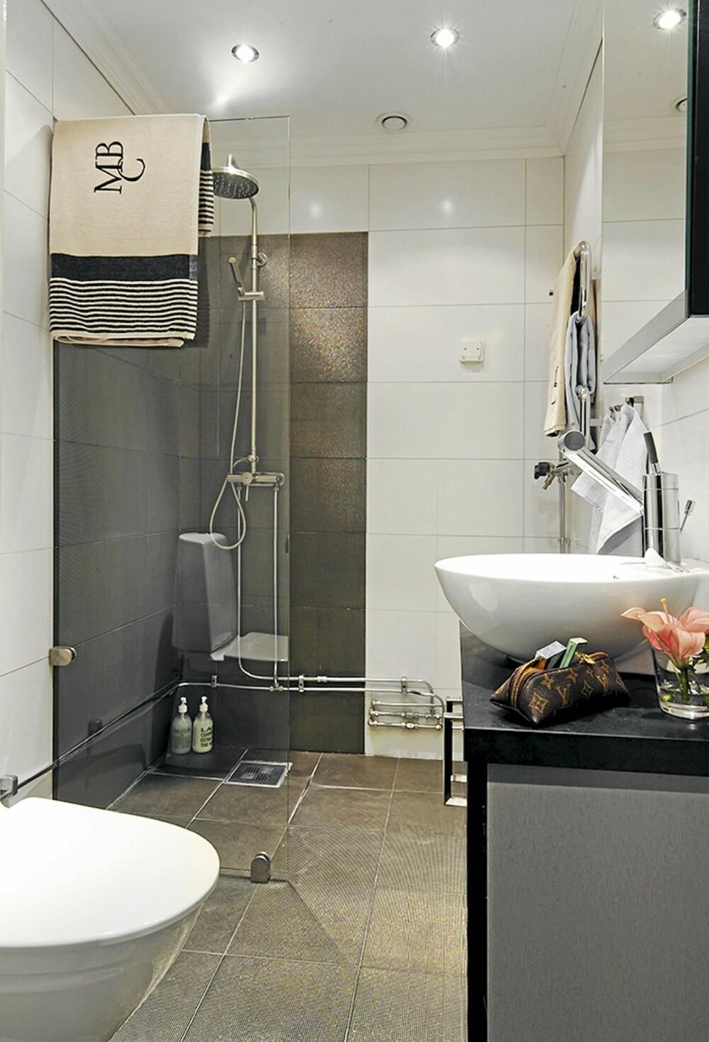 BAD: Badet er stilrent i svart og hvitt med gulldetaljer i flisene