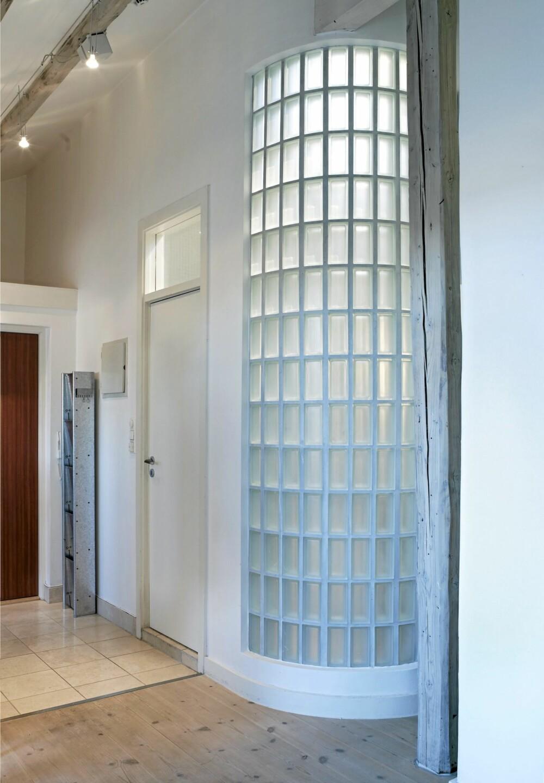 ROMARKITEKTUR: Den buede glassveggen utgjør et arkitektonisk element i leiligheten. Ved siden av å understreke takhøyden bidrar veggen til å maksimere lysinnfallet på det vindusløse badet. Et klart vindu over døra gjør samme nytte.
