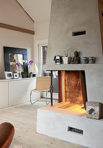 KOSELIG MED PEIS: Den murte peisen står midt i stuen. Speilet på kommoden reflekterer lyset som kommer inne fra verandaen.