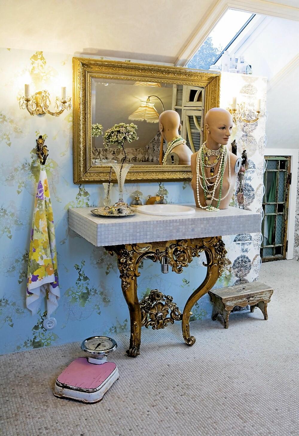 Benken på badet ser ut som et bord som kommer ut av veggen. Platen ble bygd på stedet. Understellet er et gammelt gullbelagt konsollbord. Blandebatteriet i ¿gull¿ og krystall og den gamle bysten er kjøpt billig på Ebay.