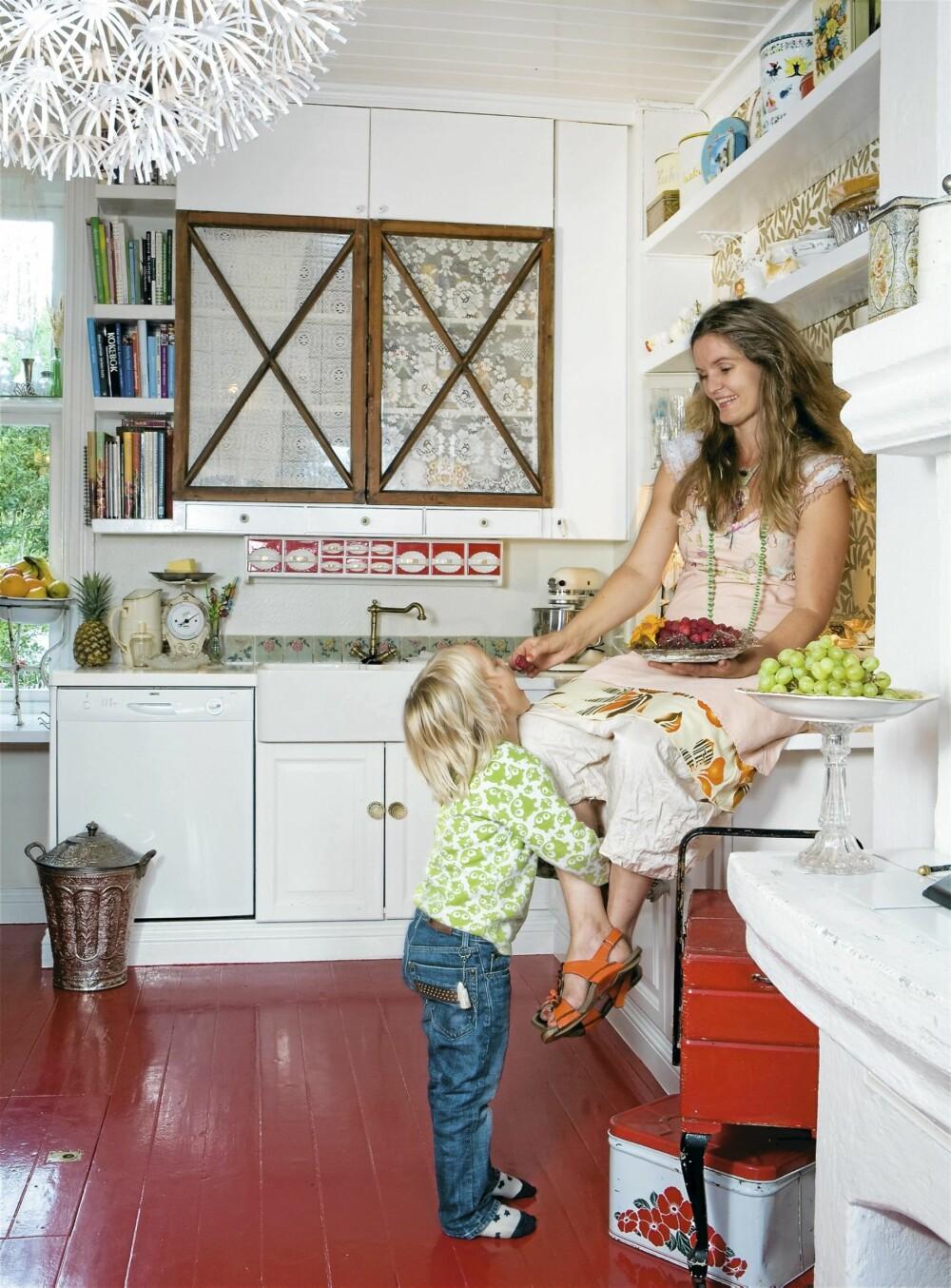 SKAPVINDUER: Skapdørene på kjøkkenet er laget av gamle vinduer med blonder stiftet fast på innsiden. Den røde krydderhyllen fikk Line av broren sin da hun fylte 40 år. Fargen på gulvet er hentet fra denne. Planen er å flytte kjøkkenet til den lyseste delen av huset.