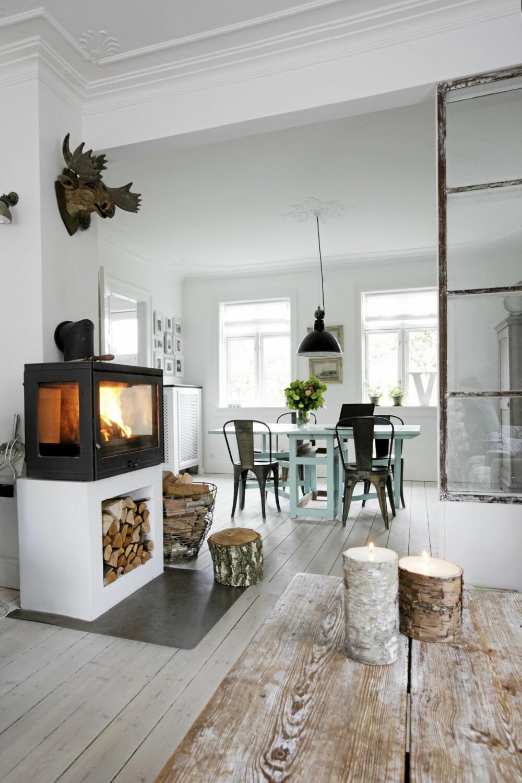 SKAPER VARME: Peisen og glassveggen gir en naturlig oppdeling av stuen. Trelysene i forgrunnen er fra Broste Copenhagen.