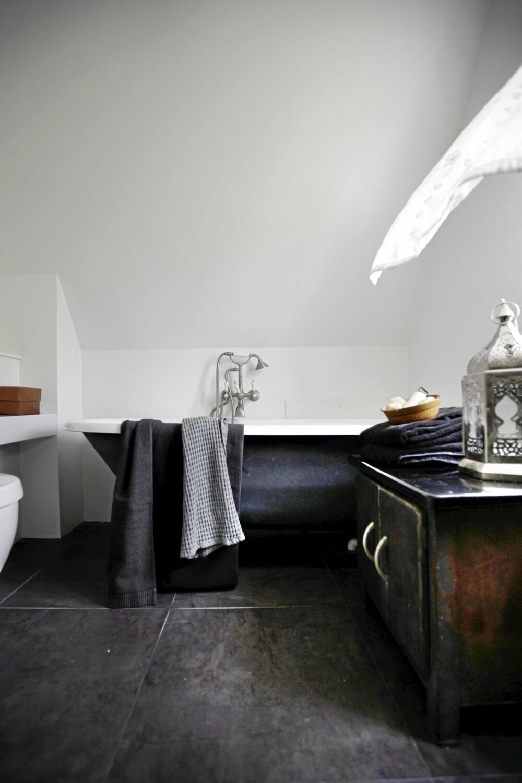 BAD MED PERSONLIGHET: De mørkegrå, matte flisene på baderomsgulvet danner en flott bakgrunn for badekaret med løveføtter. Flisene er fra Odorico.  Det vakre, gamle skapet gir også personlighet til rommet.