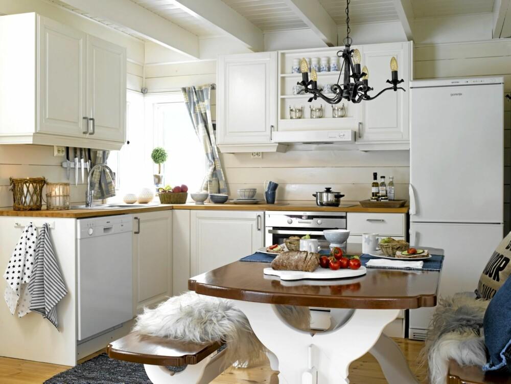 NYTT LIV: Ved å male den gamle innredningen lys, har familien Bruserud fått et nytt og sommerlig uttrykk på hyttekjøkkenet sitt. Saueskinn fra ullkilden.no, lykter og kjøkkenhåndklær fra Home & Cottage.