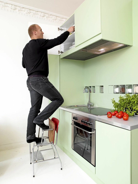 DYPE OVERSKAP: Trappestolen er en nødvendighet når Dahle skal hente ting i veggskapene. Stålnettet under veggskapene er fra Burmeister. En list skjuler ventilatoren, og et hull i nettingen sørger for tilgang til av-og-på-knappen.