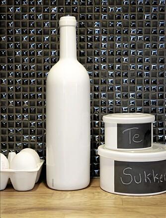 FLISESPILL. Matte og blanke fliser gir fint spill. Mosaikkflisene Dune Orion 185924 er 12 x 12 cm og kommer på 30 x 30 cm store ark, fra Bergersen. Eggebrett og flaske i porselen , fra Illums, og bokser fra Konzept HP.