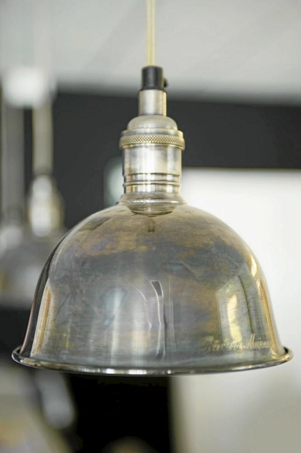 BELYSNING: God belysning er viktig på kjøkkenet, og særlig over kjøkkenbordet hvor man både spiser og arbeider. For å bryte litt med den romantiske stilen kan det være stilig med en industriell stil på belysningen. Tøffe lamper i stål og sink vil passe godt på et rustikt kjøkken. Fra Riviera Maison