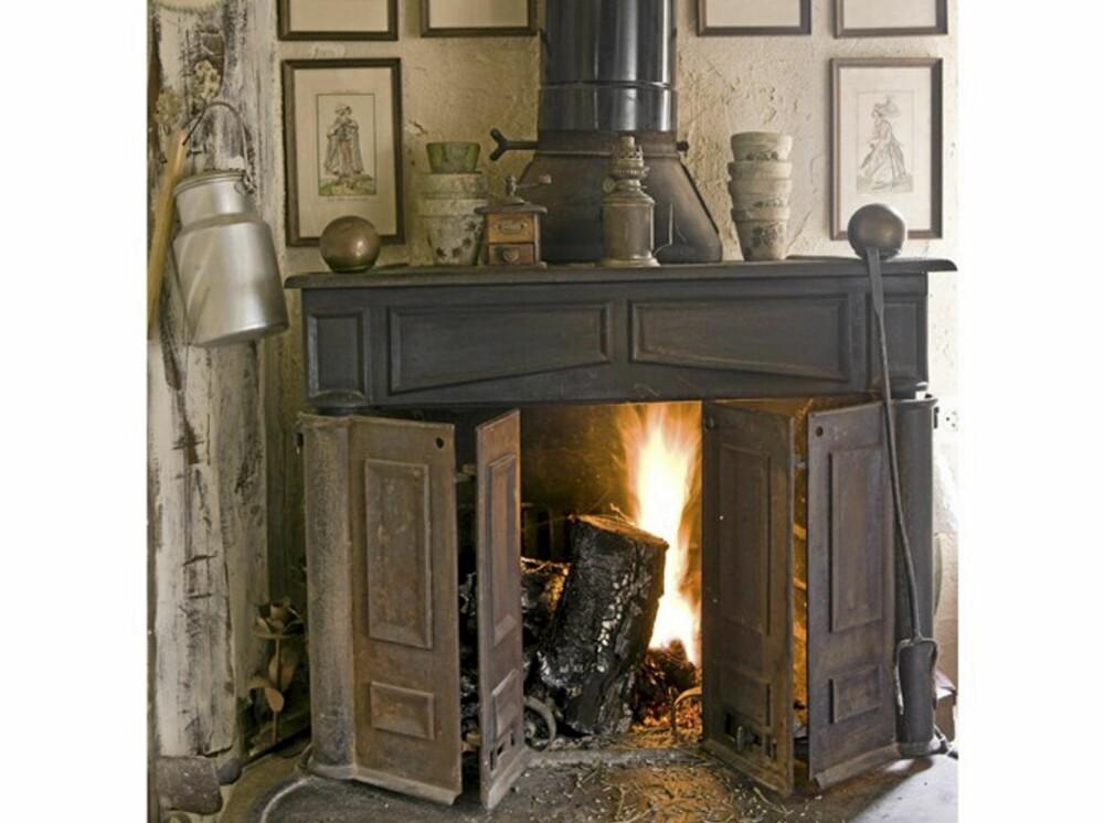 LEVENDE FLAMMER: En peis med levende flammer gjør seg på et røft og landlig kjøkken.
