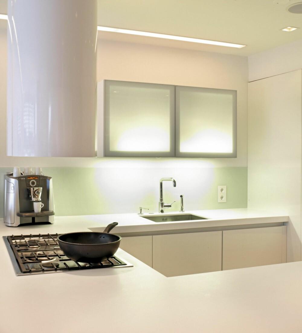 HELHVITT: Den helhvite paletten brukes som virkemiddel for å nedtone kjøkkenets tilstedeværelse i et allrom.