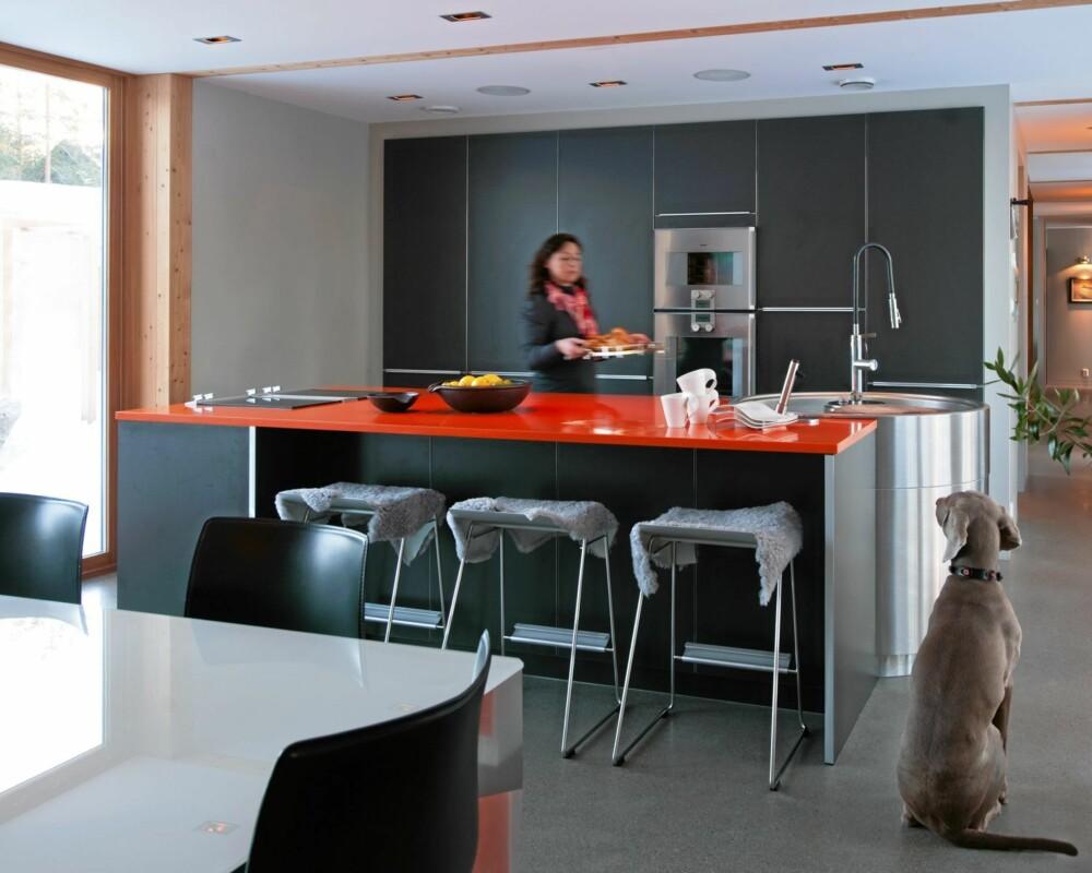 GLATT KJØKKEN MED PANGFARGER: Grått og rødoransje bringer liv og røre inn på det ellers stramme og renskårne kjøkkenet.