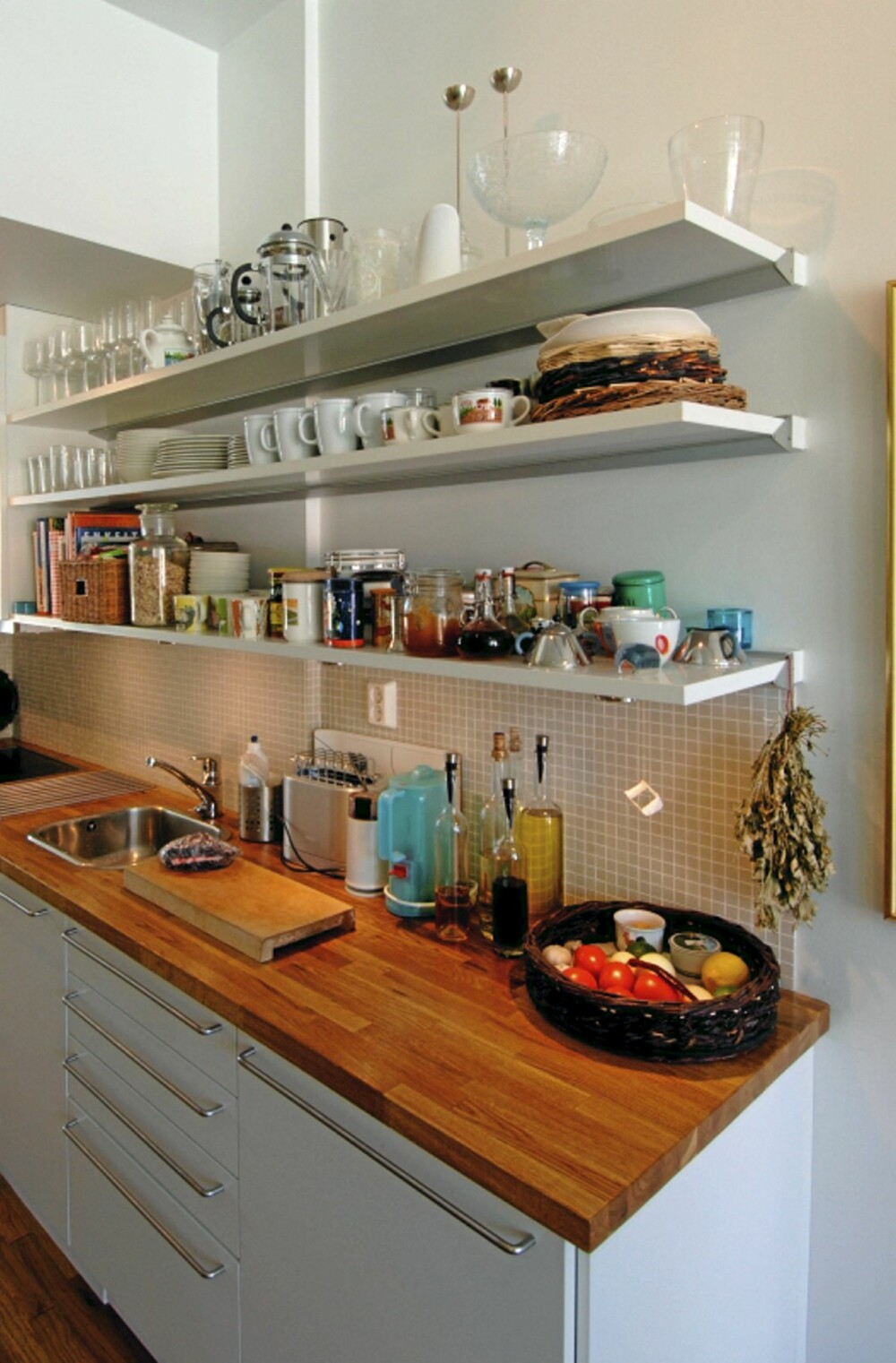LANGE HYLLER. Her er kjøkkenet smalt og avlangt og matches med tilsvarende hyller.