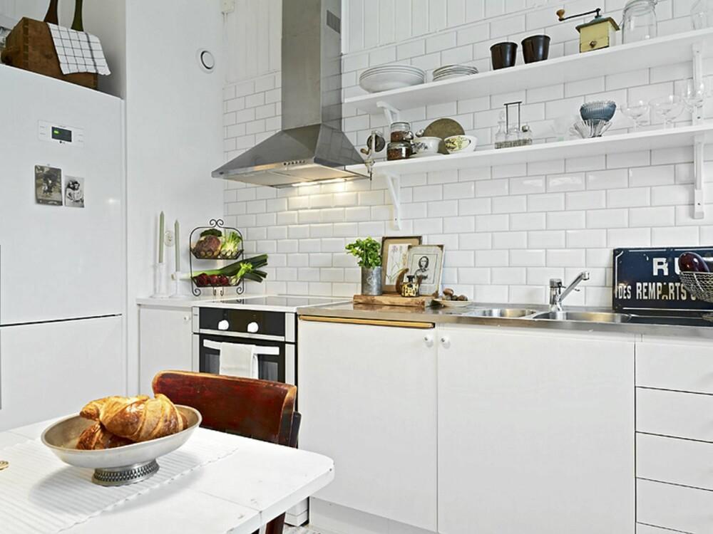 KJØKKEN: Kjøkkenet har et landlig preg med åpne hyller og hvite fliser på veggen