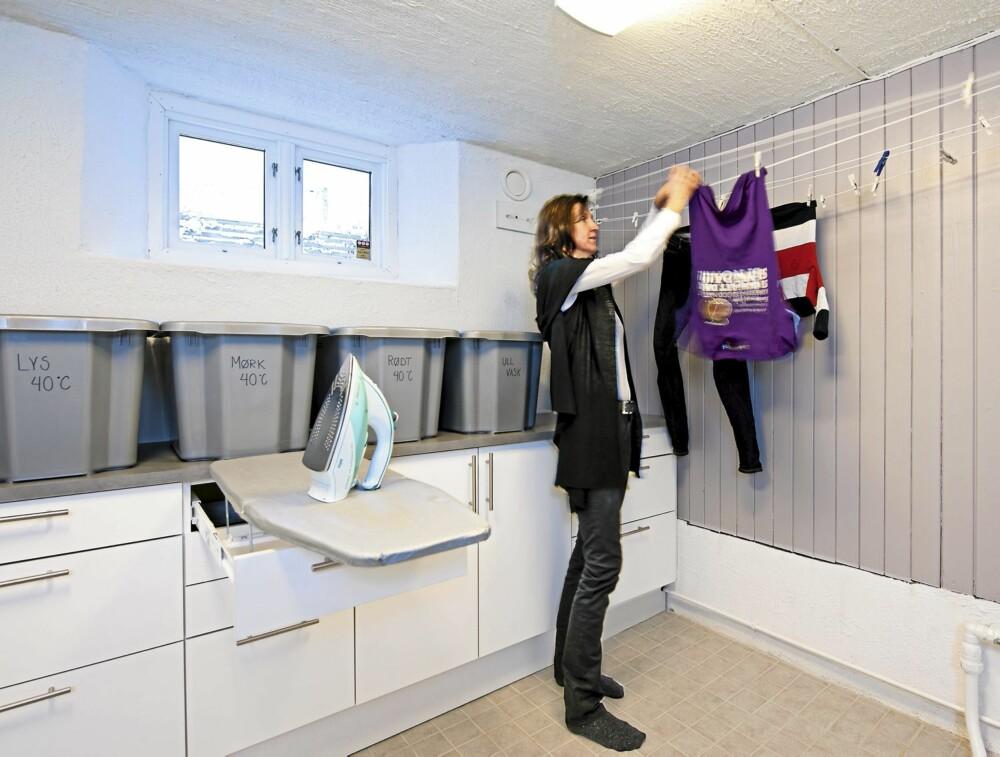 ARBEIDSGLEDE: Med gulvvarme og tradisjonelle klessnorer tørker de våte plaggene utmerket i det nyoppussete vaskerommet. Plastkasser fra Claes Ohlson.