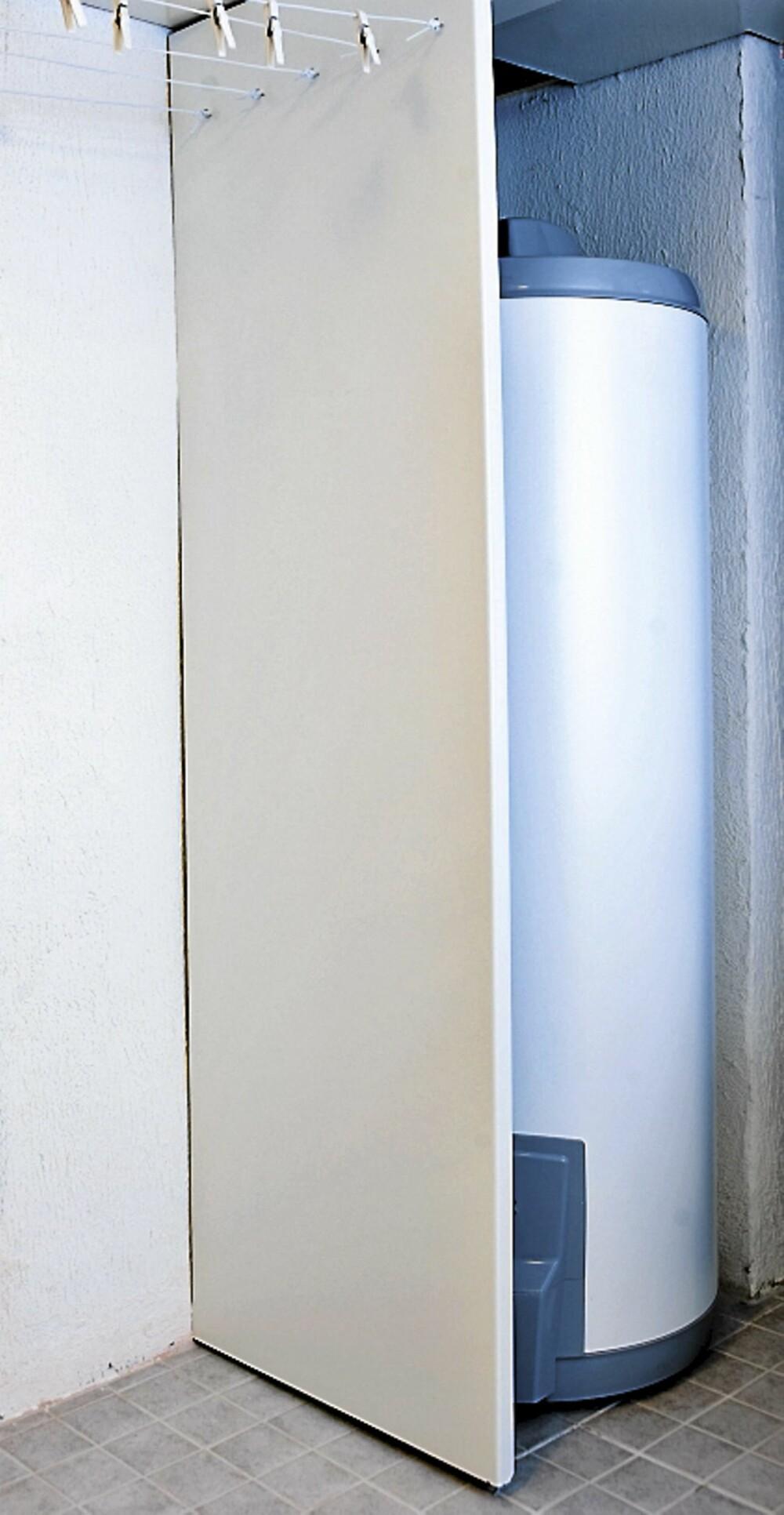 LUR LØSNING: Ved døren til vaskerommet skjules den nye varmtvannsberederen bak en benkeplate stilt på høykant. Den har metallbeslag i topp og bunn.