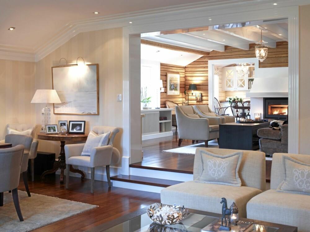 NIVÅFORSKJELLER. Stuene ligger på ulike nivåer som bidrar til en spennende løsning. Solid eik går igjen i hele huset. I den midterste stuen er tømmeret ubehandlet, mens det er malt hvitt i spisestuen.