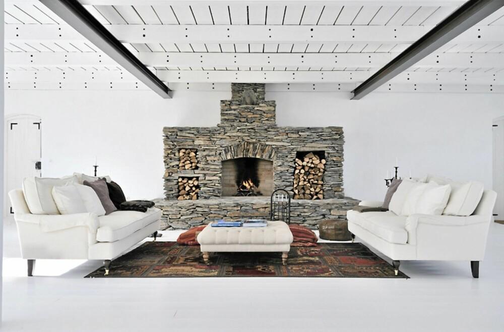 ILDSTED: Den store peisen i stein gir varme til den ellers hvite peisestuen