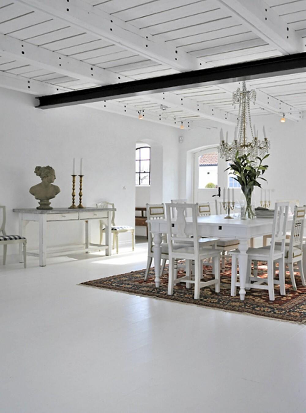 SPISESTUE: Spisestuen har et majestetisk uttrykk med de store gulvflatene og den ruvende lysekronen