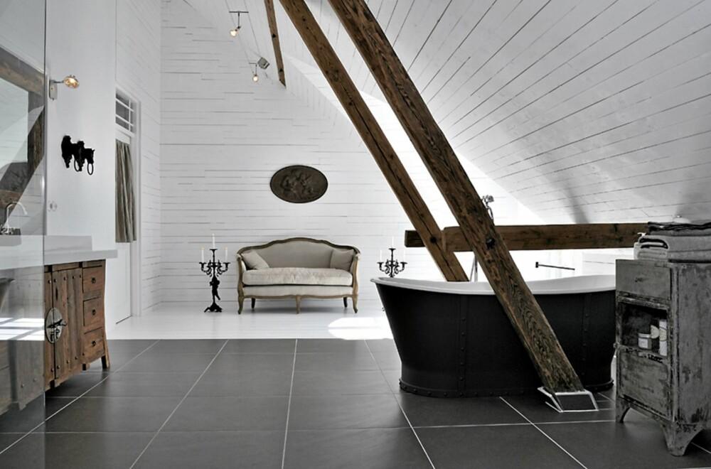 BAD: Frittstående badekar, innredning i tre og grove bjelker gir badet en eksklusiv og røff følelse