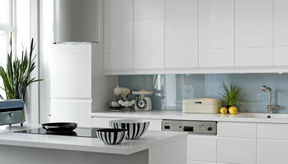 DELIKAT. Kjøkkenøya ble flyttet ut i rommet. Kjøkkeninnredning med vifte fra Kvänum. Herdet glassplate mellom over og underskap. Benkeplater fra Corian,levert fra Corinor. Armatur fra SMEG. Peisekanten skimtes til høyre.