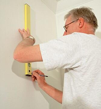 RETT: Strek opp en linje for den første tapetlengden ved hjelp av blyant og vater.