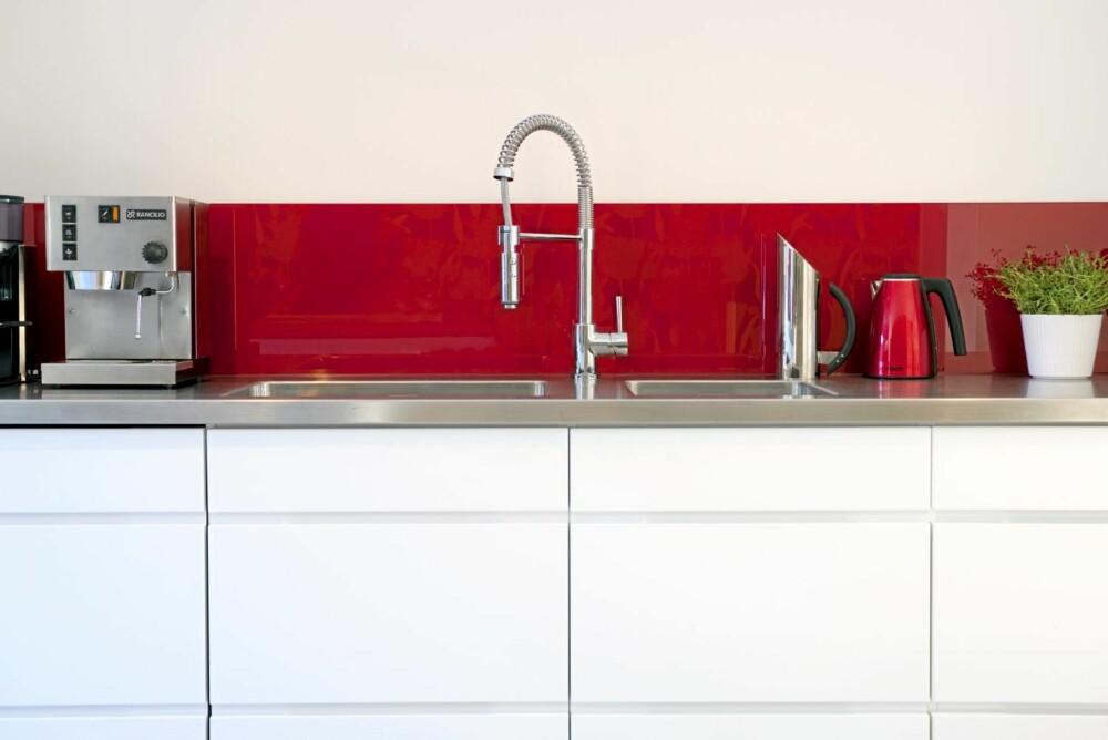 SPRUTSIKKERT. Glassplaten over komfyren er malt rød på baksiden. Innredning fra Kvik.  Glass fra Oslo Glass & Vindu.