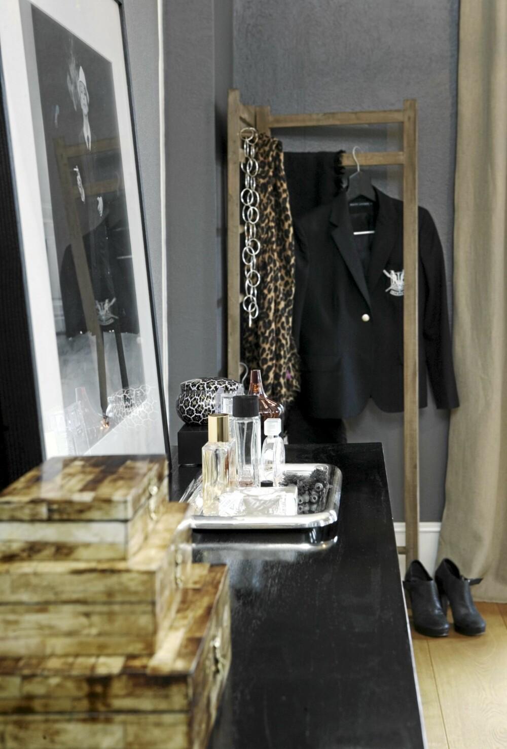 EFFEKTER: Åpen og enkel garderobe fra Ikea. På den blanke konsollen er det dandert røffe skrin, flasker og skåler.