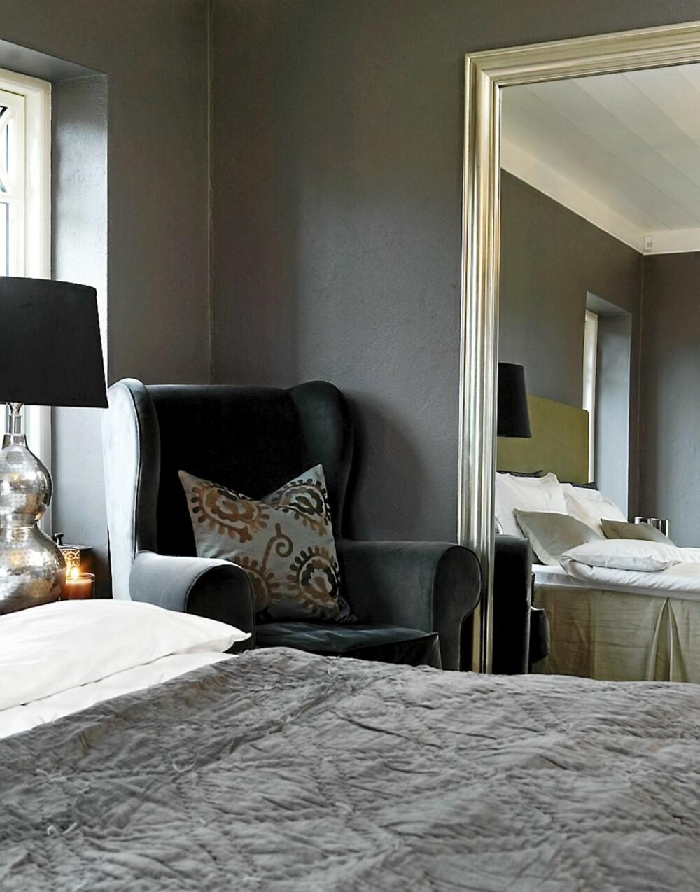 KLASSISK: Lenestol med pute, sengeteppe og nattbordlampe fra Day Home. Sengeteppe fra Sirocco og speil fra House Doctor.