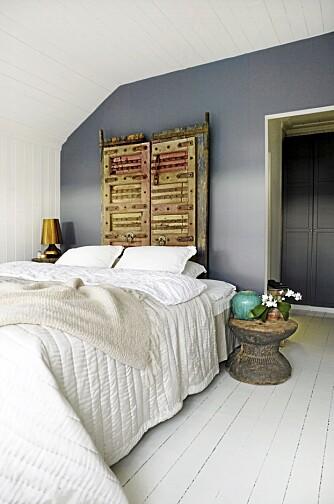 INDISKE DØRER. Sengegavlen er lagd av to gamle dørblad fra India. Den gråblå veggen er nylig malt, du kan prøve Sens 4618 Kveldshimmel fra Jotun for å få lignende farge. Gulvet er originalt, fra da huset ble bygd i 1910. Det strikkede sengeteppet er håndarbeid fra Nepal. Nattbordet er en indisk morter som er snudd opp/ned.