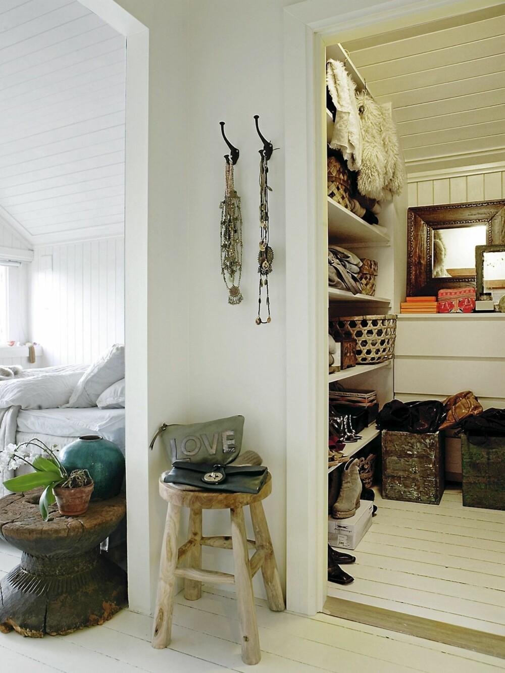 ALT I ETT. Anna har en liten gang og et garderoberom som er tilknyttet soverommet. Krakken er lagd av teakrøtter fra Indonesia. Smykkene er fra egen butikk. Kassene med vesker er egentlig blomsterkasser som har fått ny bruksverdi.