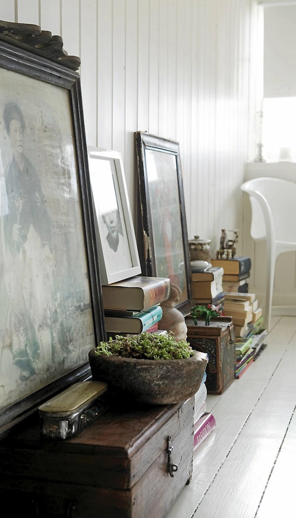 BOKHYLLER PÅ GULVET: Anna har droppet bokhyller og stabler heller bøkene langs veggen sammen med bilder og gjenstander fra reiser.