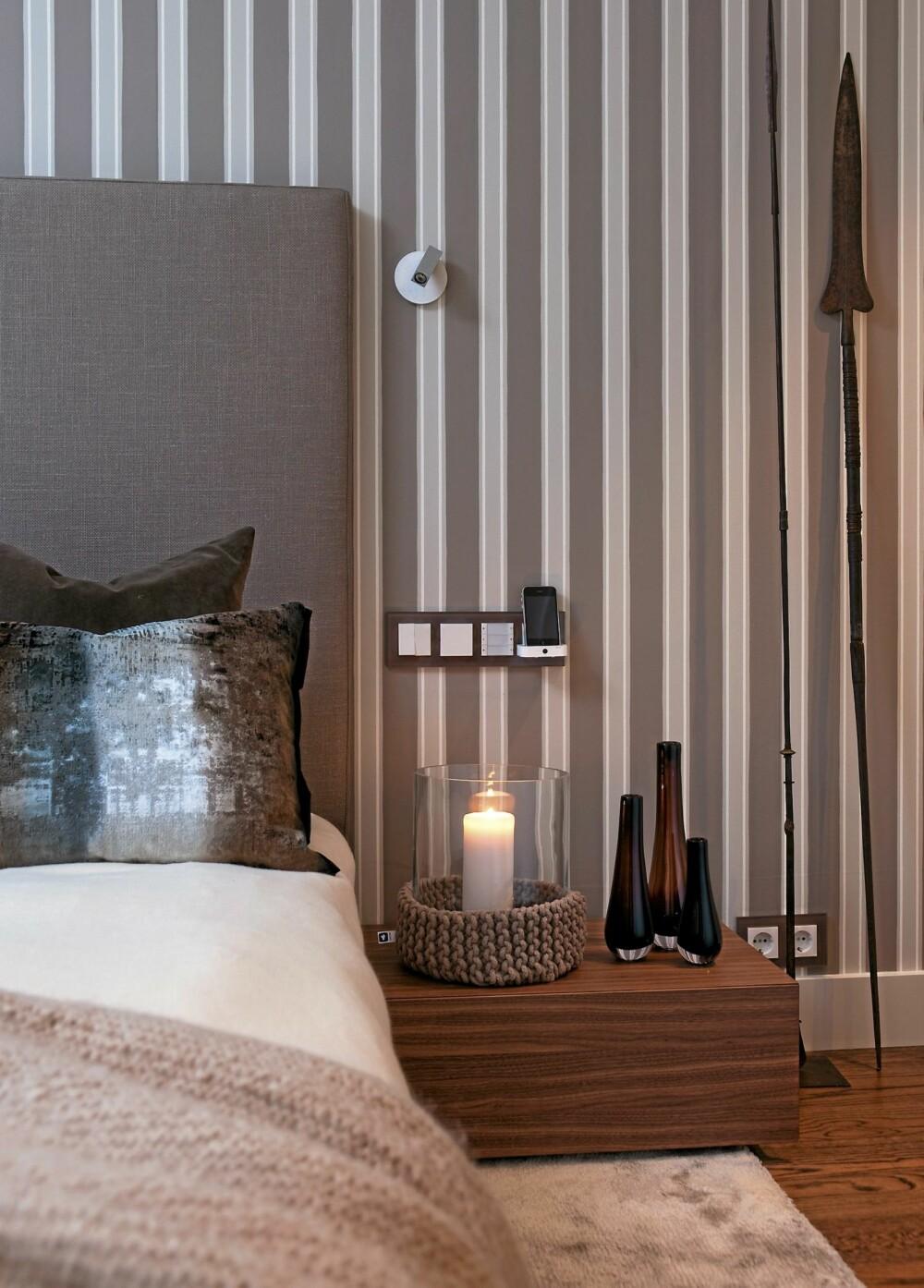 SMART ORDNING. Tapetet bak sengegavlen har striper i samme farge som veggen. Bryterne og mobilladeren ved siden av sengen har passe høyde over nattbordet. Bryterne Gira Espirit fra Mico Matic har dekorative glassrammer.
