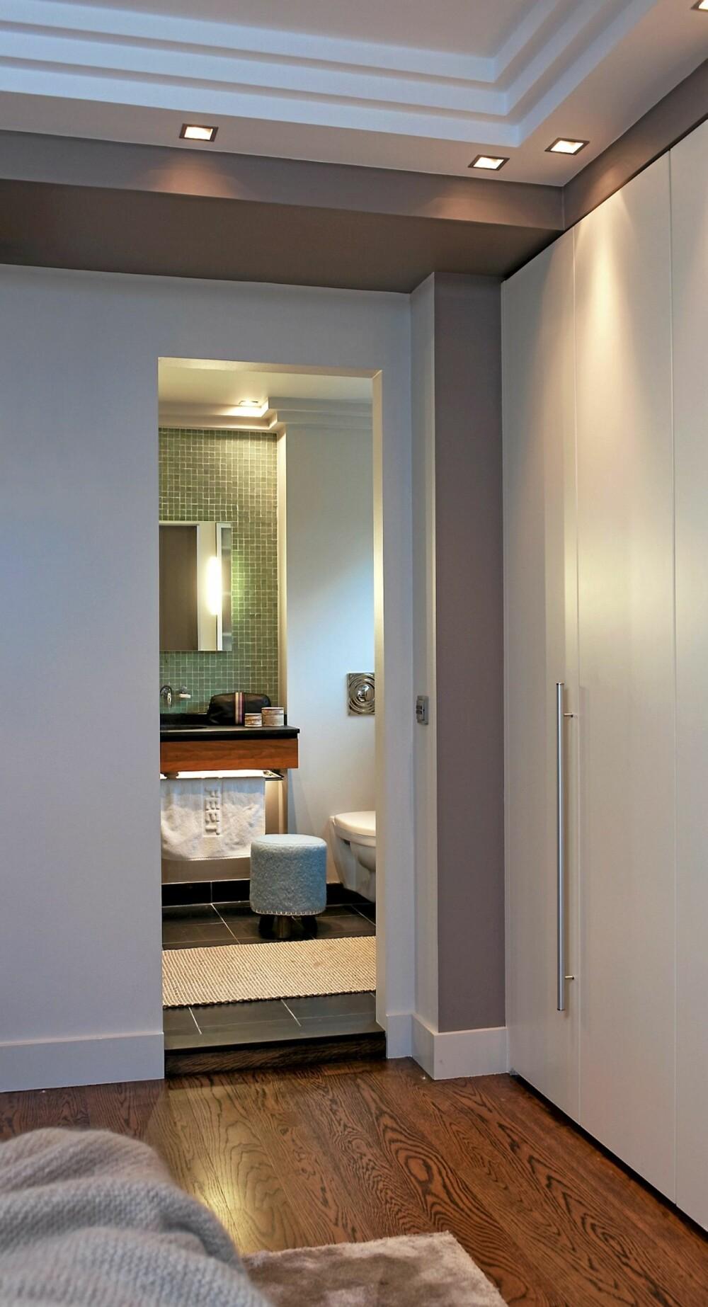 UTEN EN DØR. Soverommet er tilknyttet eget bad, og døren mellom rommene er fjernet. Det slipper inn lys samtidig som det også sparer plass. I og med at man kan se skrått inn til toalettet fra det ene soveromsvinduet, er det bryter til de elektriske liftgardinene på badet slik at man kan bli skjermet for innsyn. Nedtrappingene i taket med downlight er et dekorativ element. Garderobeskapene fra gulv til tak har fått kontrastfarge rundt, det samme har nedfellingen på himlingen.