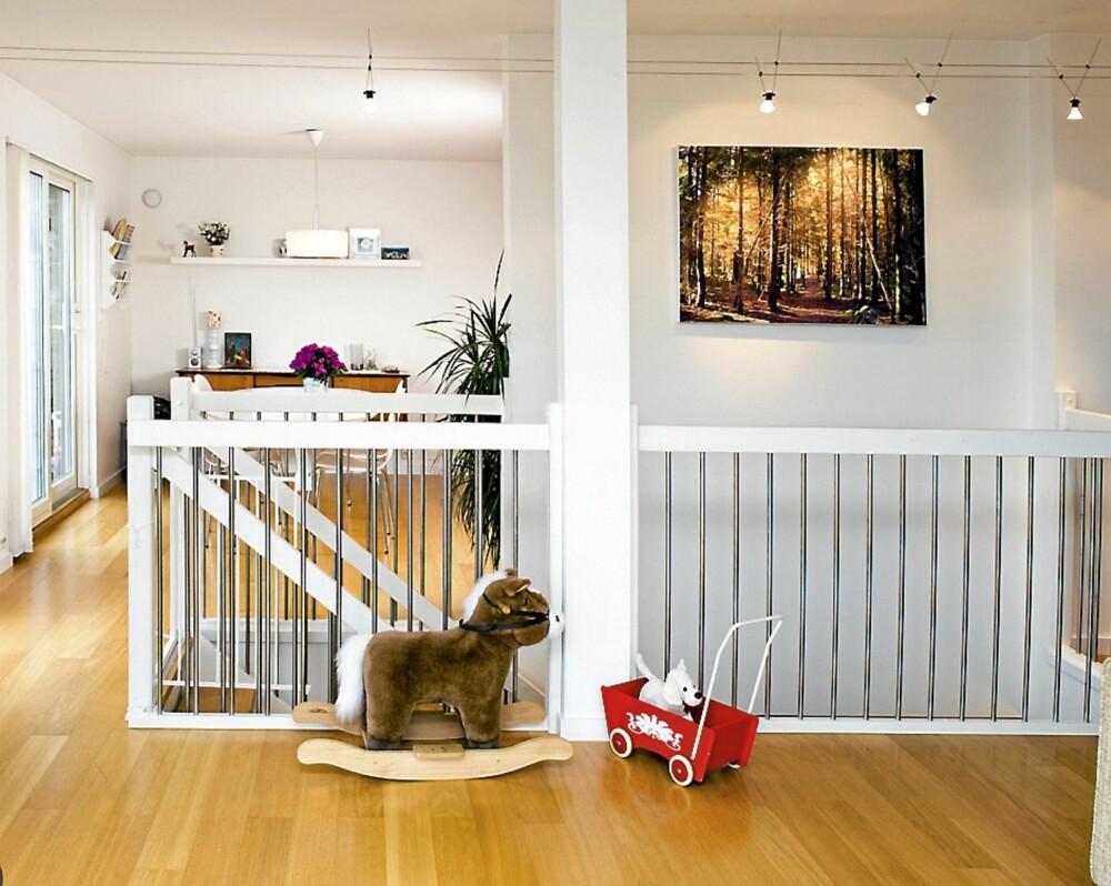 TILPASNINGER: Huset kom med eikeparkett og hvite vegger. På grunn av barna har Mette og Åsmund montert en grind fra Ikea foran den bratte trappen. Bildet på veggen er fra skogen utenfor huset, og er tatt av Mette.
