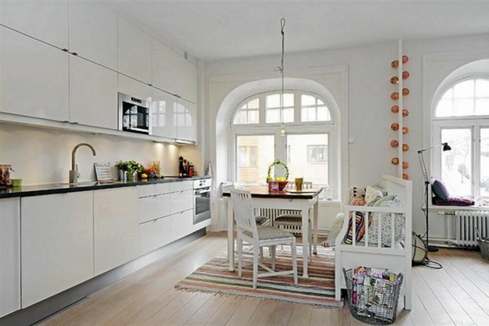 ROMDELER: Den hvite sittebenken fungerer som en romdeler mellom den åpne stue og kjøkkenløsningen.