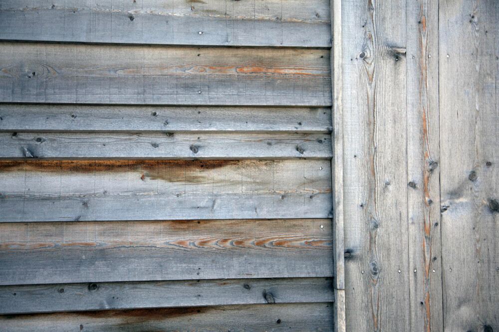 KOMBINASJON: Hytta er kledd i lerk som har grånet med tiden. Den gamle hytta hadde liggende panel, mens den nye delen har fått stående. Det skaper en spennende overgang.