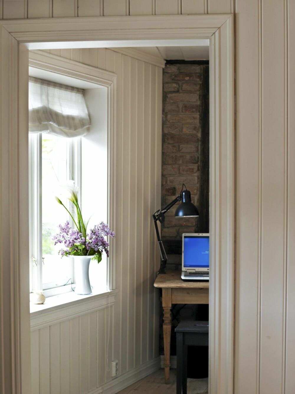 PANEL OG TEGL: Hvitmalt panel øker romfølelsen mens naken murstein fremhever historien. Rommet innenfor stuen brukes som hjemmekontor.