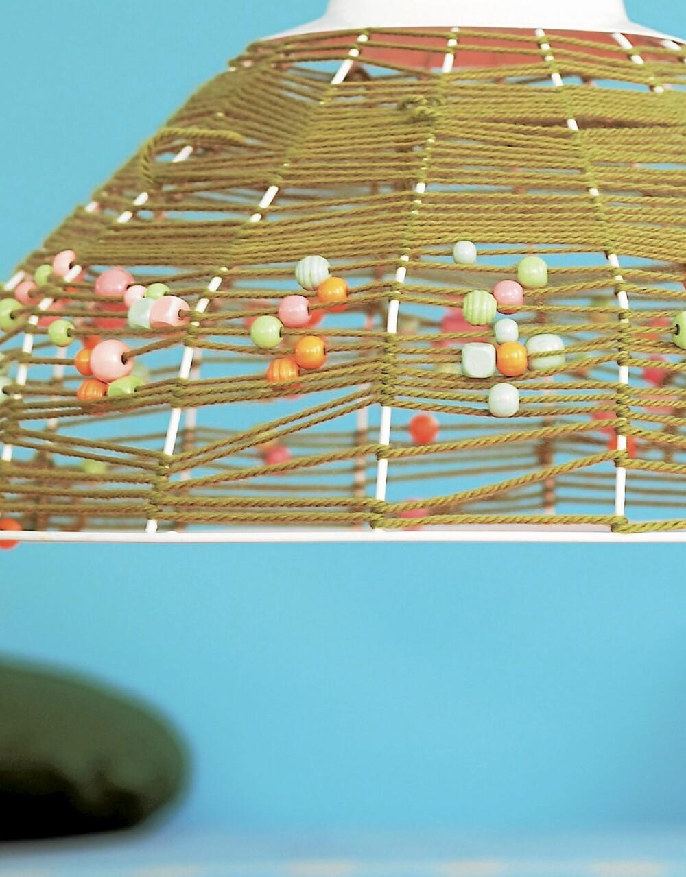 LAG KUL LAMPE: Du trenger et lampeskjelett av wire, ca. kr 530, House Doctor/Tina Sand, et olivengrønt garn og pastellfargede perler, fås hos Panduro Hobby. Start med å binde fast garnet øverst på lampen og surr det halvveis ned på stativet. Træ perler tett i tett på tråden og surr cirka en fjerdedel til. Træ nå færre perler på tråden og surr det siste stykket. Bind fast garnet i enden.
