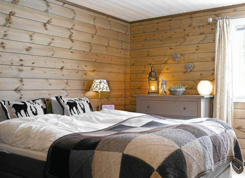 HJEMMESTRIKKET: På gjesterommet har Bjørg strikket sengeteppe og sydd pynteputer. Hun kaller sengeteppet et kombiteppe, siden hun også bruker det som pledd i stuen.