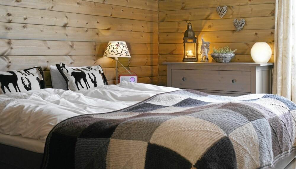 RUSTIKT OG HJEMMELAGET: Den store sengen på soverommet har blitt dekorert med hjemmelagde tekstiler. Eieren har nemlig både sydd rådyrputene og strikket sengeteppet.