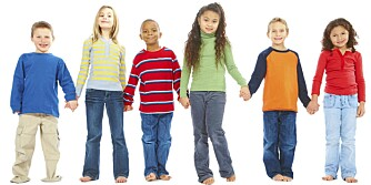 Portrait of group of young children holding hands together over white background