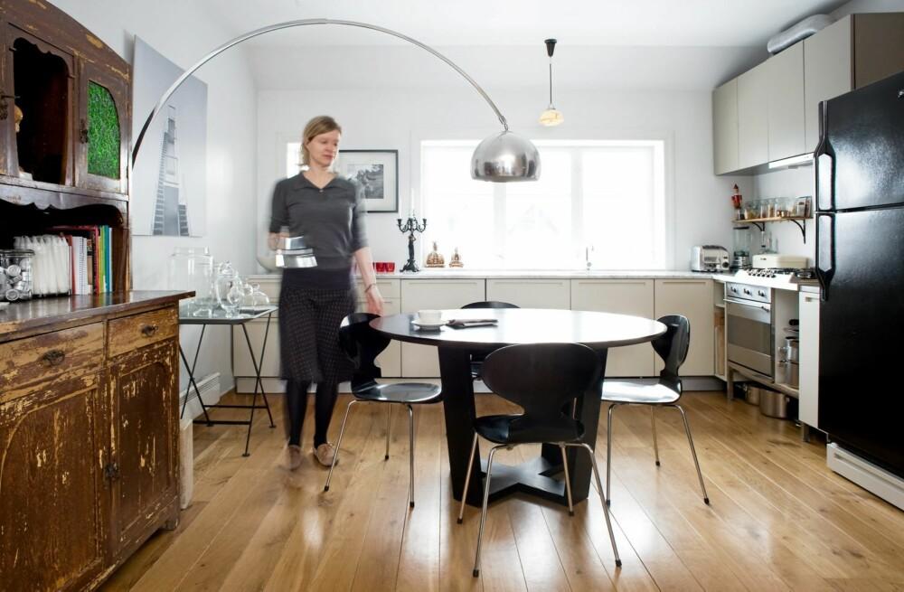 OPPHOLDSROM OG SPISEPLASS: Kjøkkenet er navet i boligen, her er aktivitetsnivået høyest. Skallstolene fra Fritz Hansen er kjøpt brukt, i likhet med det runde bordet. Framskapet og kopien av lampen Arco er kjøpt på nettauksjonen lauritz.com.