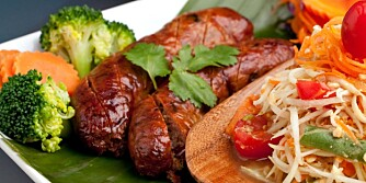 Plate of freshly prepared Thai sausage and som tum green papaya salad.