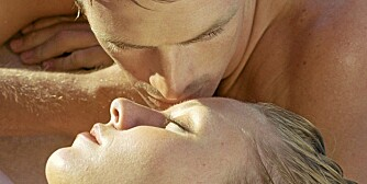 Couple lying down, man kissing woman's forehead, close-up