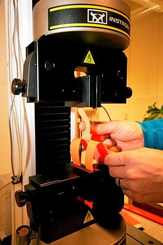 MÅLER SLITESTYRKE: Ved å klippe opp stoffprøver og feste det i denne strekkmaskinen, kan man måle nøyaktig hvor mye stoffet tåler før det spjærer.