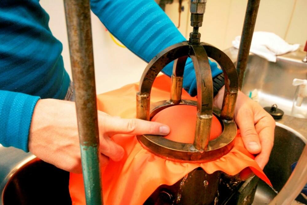 SJEKKER VANNTETTHET: Stoffet settes under vanntrykk nedenfra, til det buler en stor kul i prøven. Øyvind måler hvor mye trykk han må sette før vannet trenger gjennom.