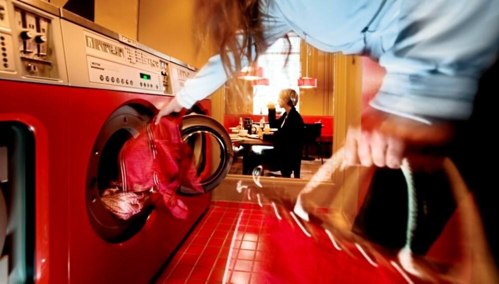 KAFFEVASK: The Laundromat Cafe på Nørrebro. En ung dame fyller opp vaskemaskinen mens en annen drikker kaffe.