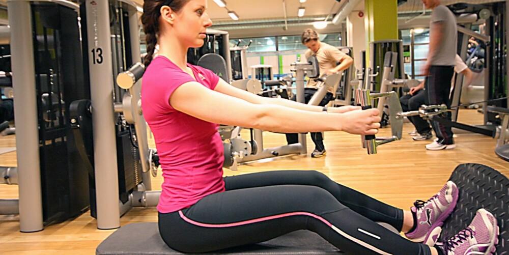 LAVTSITTENDE ROING: Sitt med føttene mot fotbrettet og trekk håndtaket ut fra apparatet ved å strekke i hofte og knær.