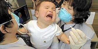 TESTES FOR INFLUENSA: Sør-Koreansk helsepersonell forsøker å ta en prøve av en baby som har ankommet med fly fra USA.