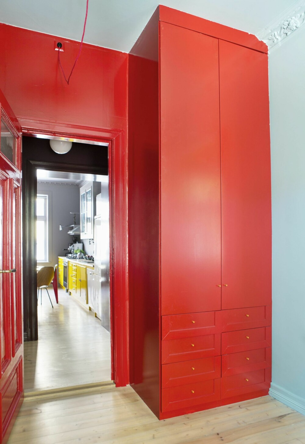 DØREN UT MOT DEN LILLA GANGEN FRA BARNEROMMET: Leiligheten er fargesatt slik at du i alle rom kan se flere av fargene på en gang. På barnerommet er rødfargen fra gangen trukket inn på den veggen som vender ut mot gangen. I bakgrunnen skimtes kjøkkenet, med knallgule underskap. Styling: Tone Kroken.
